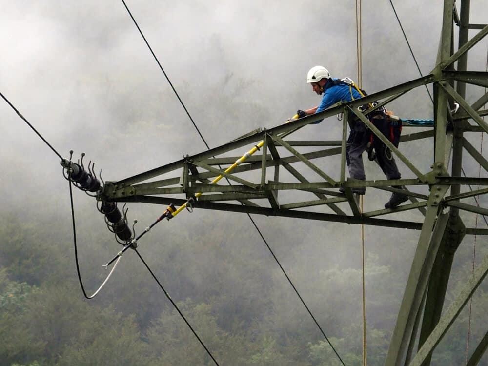 Ein Netzmonteur stellt in luftiger Höhe sicher, dass die Leitung tatsächlich nicht unter Strom steht